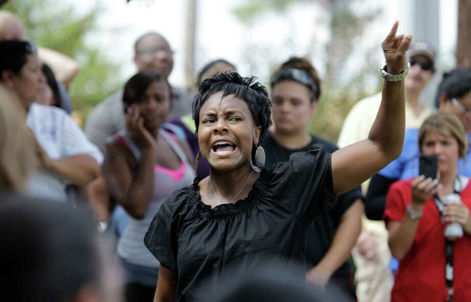 Tammi Humphrey speaks about the need to make a difference and attend school board meetings to a crowd of people waiting across the street from Spring High School where a student was fatally stabbed and three others injured Wednesday, Sept. 4, 2013, in Spring. Photo: Melissa Phillip, Houston Chronicle / © 2013  Houston Chronicle