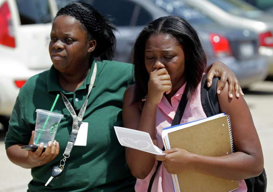 A woman and girl, who would not give their names, leave after students were released from Spring High School where a student was fatally stabbed and three others injured Wednesday, Sept. 4, 2013, in Spring. Photo: Melissa Phillip, Houston Chronicle / © 2013  Houston Chronicle
