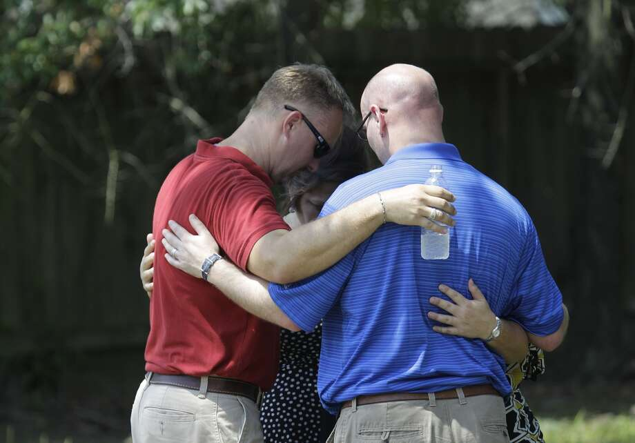 Joel Eisenbraun, left, and John Cordrey, right, both with Trinity Lutheran Church pray with others outside Spring High School where a student was fatally stabbed and three others injured Wednesday, Sept. 3, 2013. Church members have been at the site passes out bottles of water. (Melissa Phillip/ Houston Chronicle)