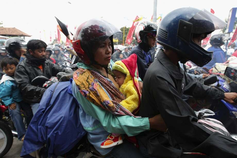 A mother breast-fed her baby on top of a motorcycle, joining the traffic migrating for the annual Muslim festival Eid on September 27, 2008, in Gilimanuk, Bali Island, Indonesia. The photo went viral and raised awareness about  motorcycle deaths during the Eid journey. The total number of casualties from 2007's Eid migration was 789 deaths with 90% of those deaths involving a motorcycle. Photo: Dimas Ardian, Getty Images