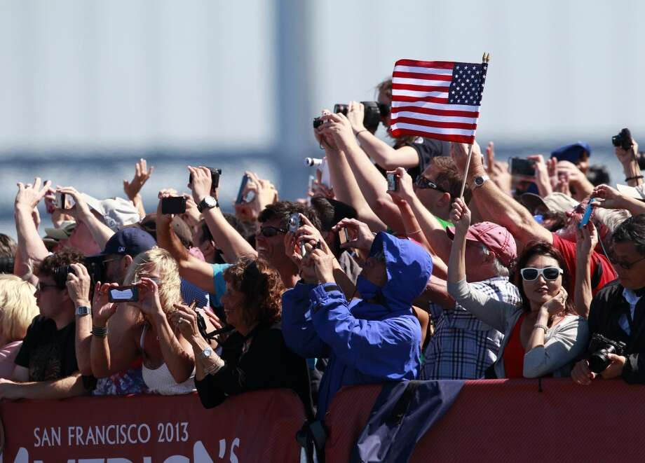Spectators wave as Oracle Team USA passes by after winning Race 4 of the America's Cup Finals on Saturday, September 8, 2013 in San Francisco, Calif. (Beck Diefenbach/Special to the Chronicle) Photo: Beck Diefenbach, Special To The Chronicle