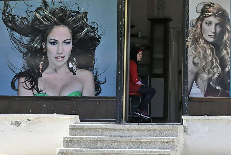 Our special today is the 'Jennifer Lopez in a Convertible':A hairdresser waits for clients at her   salon in Hatay, Turkey. Photo: Gregorio Borgia, Associated Press
