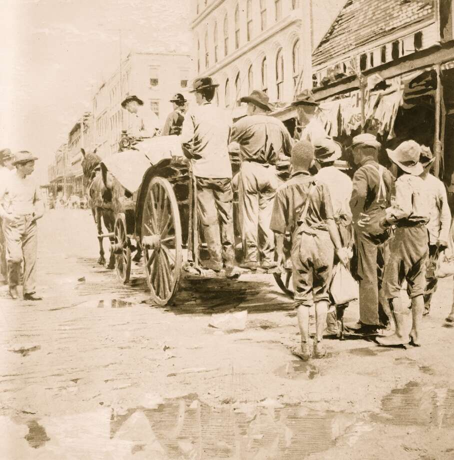 September 1900: Men ride behind a horse drawn cart as they gather up the dead from Galveston streets, after the devastating hurricane. Photo: Buyenlarge, Getty Images