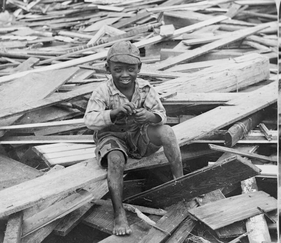 UNITED STATES - CIRCA 1900:  African American boy, sitting on debris in the wake of the 1900 hurricane, Galveston, Texas.  (Photo by Buyenlarge/Getty Images) Photo: Buyenlarge, Getty Images