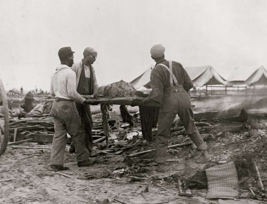 September 1900: African American men carry a body on a stretcher, surrounded by wreckage of the hurricane and flood in Galveston, Texas. Photo: Buyenlarge, Getty Images