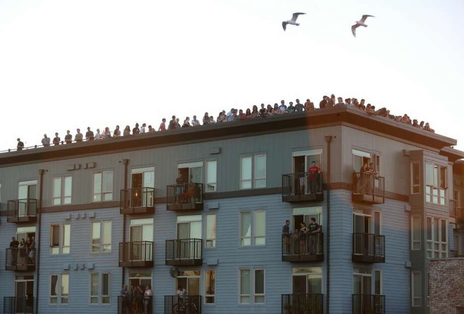 People gather on the roof of an apartment building on Wednesday near the Capitol Hill Dick's Drive-In. Photo: JOSHUA TRUJILLO/SEATTLEPI.COM