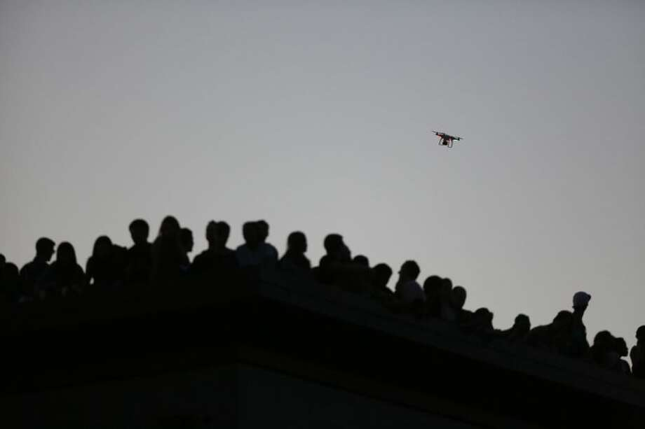 A quad-copter carrying a camera flies over the crowd on Wednesday near the Capitol Hill Dick's Drive-In. Photo: JOSHUA TRUJILLO/SEATTLEPI.COM