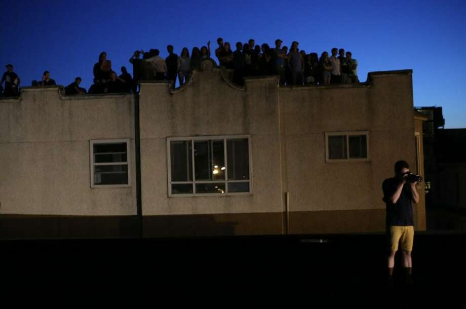 People gather on nearby rooftops on Wednesday at the Capitol Hill Dick's Drive-In. Photo: JOSHUA TRUJILLO/SEATTLEPI.COM