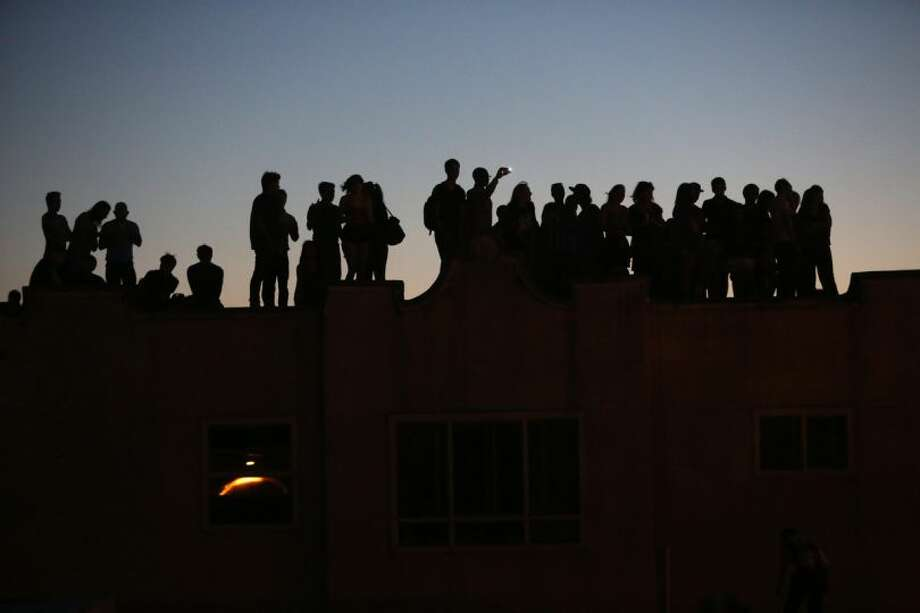 People gather on nearby rooftops. Photo: JOSHUA TRUJILLO/SEATTLEPI.COM