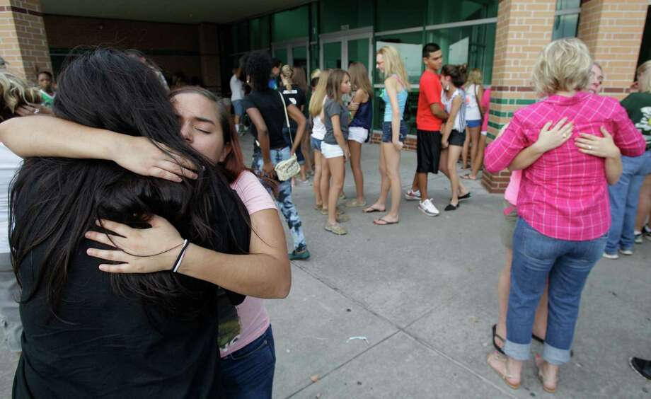 Irene Galindez, left, hugs her daughter's friend, Vanessa Rodriguez, a senior, as more than 200 people gathered for prayers outside Spring High School Sunday, Sept. 8, 2013, in Spring. Students will return to classes on Monday to the school where Joshua Broussard, 17, a Spring High School student was fatally stabbed and three others injured at the school Wednesday, Sept. 3, 2013.  Luis Alonzo Alfaro, 17, has been charged with murder. Photo: Melissa Phillip, Houston Chronicle / © 2013  Houston Chronicle