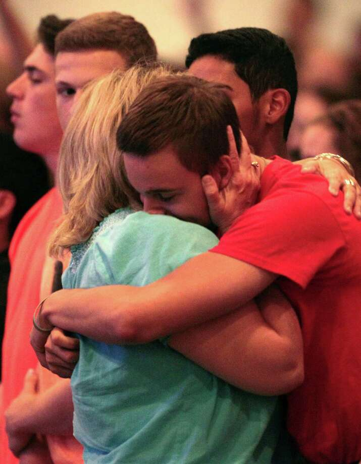 Spring High student  Zach Sckittone gets a hug from one of his teachers at the service. Photo: Billy Smith II, Chronicle / © 2013 Houston Chronicle