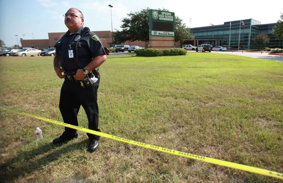 A police officer guards the perimeter of Spring High School where a fatal stabbing occurred due to an altercation between student in the cafeteria on Wednesday, Sept. 4, 2013, in Spring. Photo: Mayra Beltran, Houston Chronicle / © 2013 Houston Chronicle