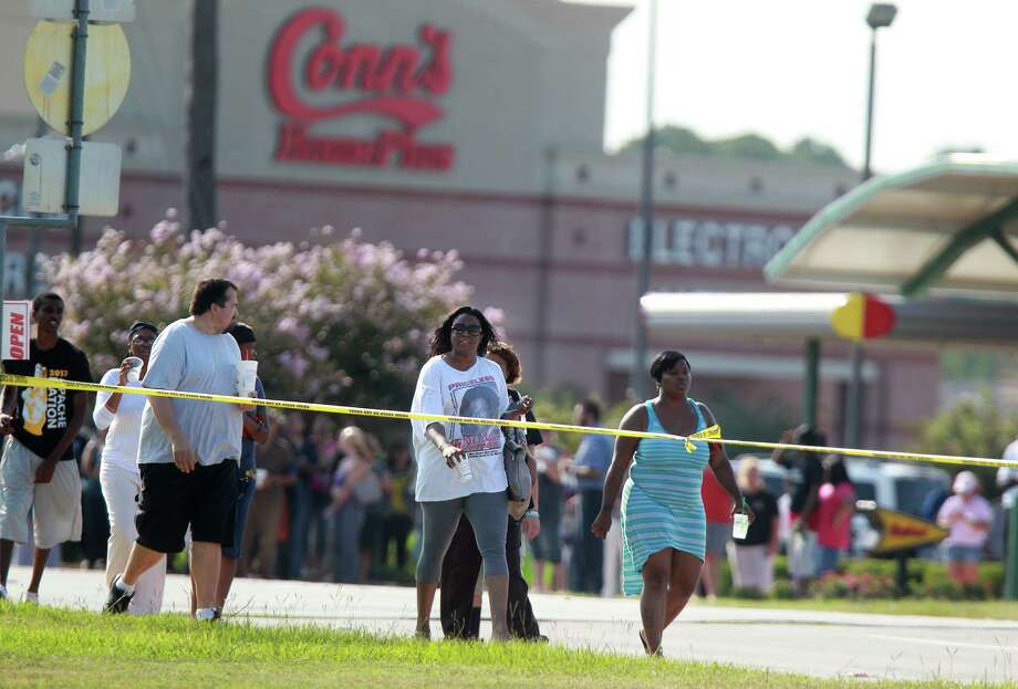 Parents were asked to wait for student dismissal across the street from Spring High School at the Conn's shopping center after a 17 year-old student was fatal stabbed during an altercation in the cafeteria on Wednesday, Sept. 4, 2013, in Spring. Photo: Mayra Beltran, Houston Chronicle / © 2013 Houston Chronicle