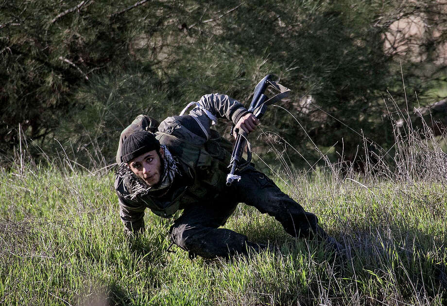 In this Saturday, Dec. 15, 2012 photo, a Free Syrian Army fighter takes cover during heavy clashes with government forces at a military academy besieged by the rebels north of Aleppo, Syria. Free Syrian Army fighters took control over the military academy after battling government forces for several hours. Photo: Narciso Contreras, ASSOCIATED PRESS / AP2012