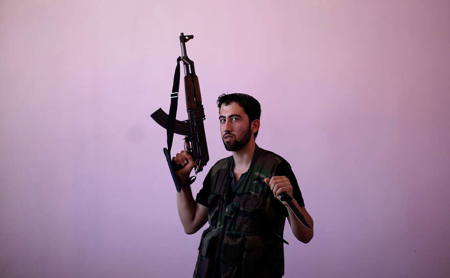 Syrian rebel fighter, Wisam Al-Saleh, 21, poses for a picture, after returning back from fighting against Syrian army forces in Aleppo, at a rebel headquarters in Marea on the outskirts of Aleppo city, Syria, Sunday, Aug. 26, 2012. In their previous lives, they were butchers, barbers, construction workers and university students. Now they are rebels fighting a civil war they hope will end the regime of Syrian President Bashar Assad. Photo: Muhammed Muheisen, ASSOCIATED PRESS / AP2012