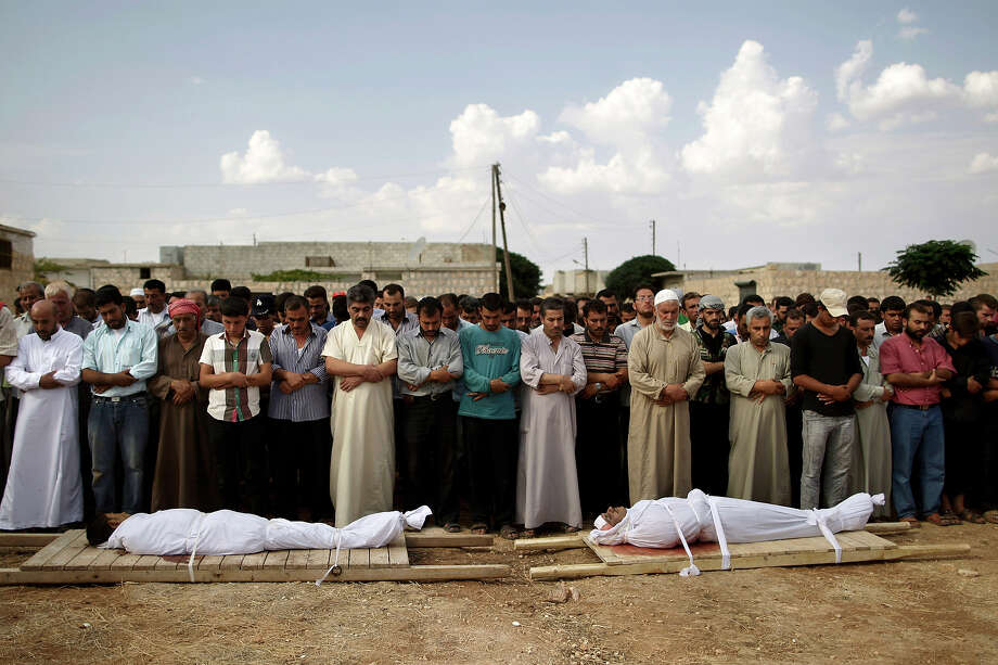 Relatives and mourners of Abdullah Alrayzar, 23, left, and Mohammed Abdul Samee, 35, pray during a funeral for four men, who were killed in a government airstrike in Marea, on the outskirts of Aleppo, Syria, Tuesday, Sept. 11, 2012. Photo: Muhammed Muheisen, ASSOCIATED PRESS / AP2012
