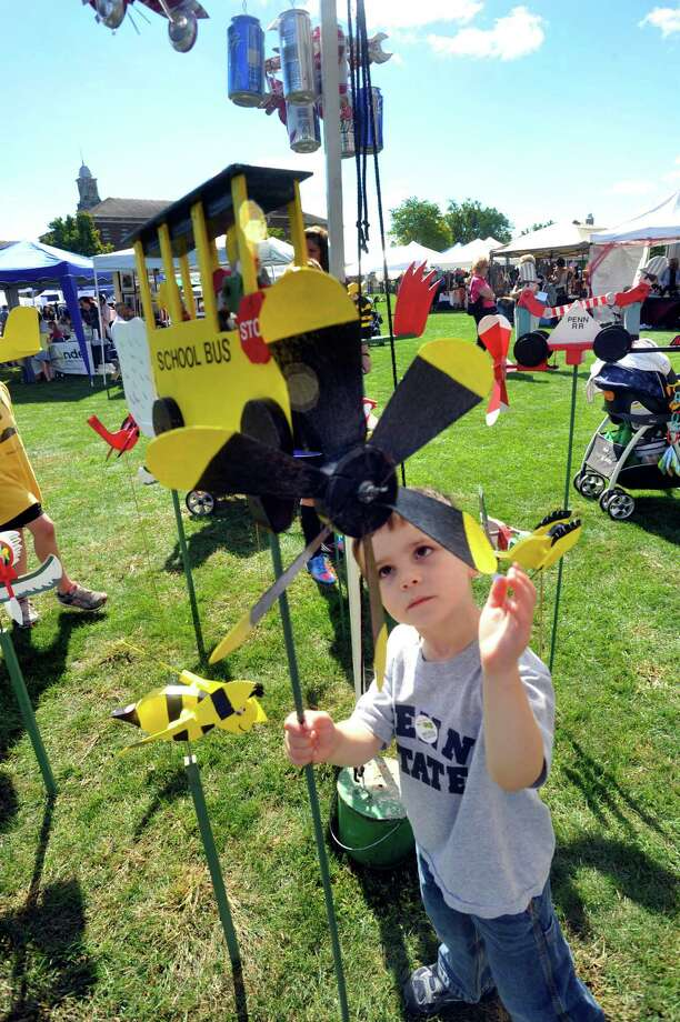 Some artistic wind-powered creations capture the attention of a young visitor at last fall's Newtown Arts Festival. This year's two-day festival will be Saturday and Sunday, Sept. 21 and 22. Photo: Michael Duffy / The News-Times