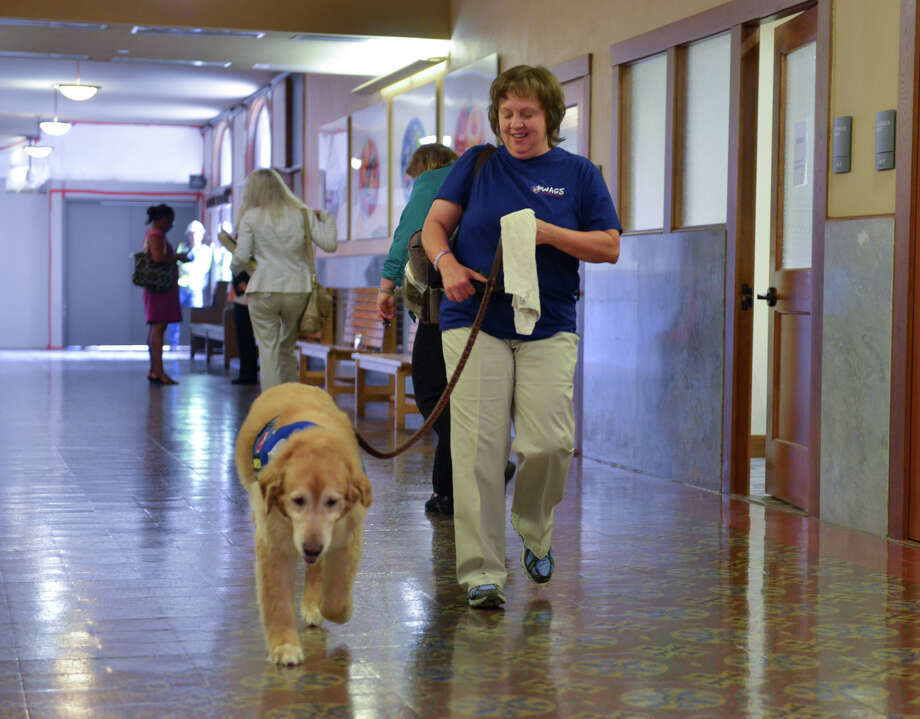 Becky Snodgrass and her therapy dog Sampson walk down a hall in the Bexar County Courthouse. Photo: Robin Jerstad