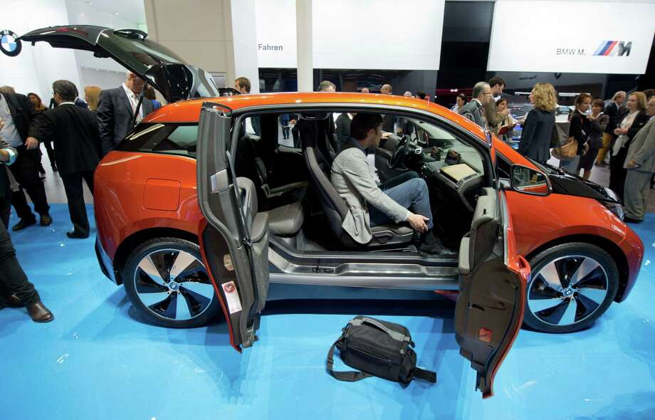 Journalists view the BMW i3 electric car at the Frankfurt Motor Show (IAA) in Frankfurt, Germany, Monday, Sept. 9, 2013.  Photo: AP