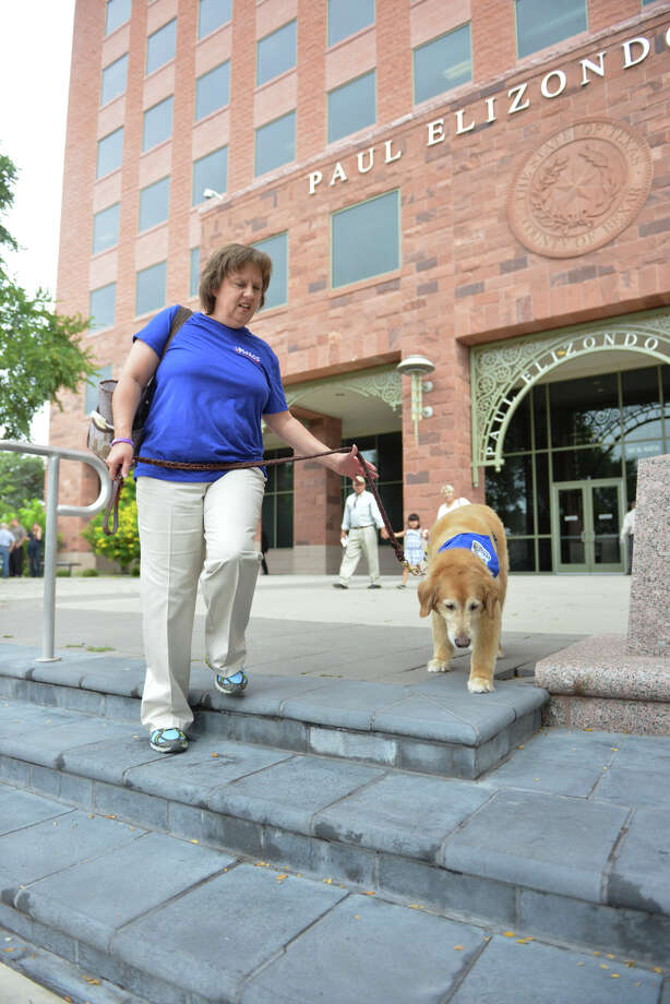 Becky Snodgrass and her therapy dog Sampson leave the Paul Elizondo Courthouse. Photo: Robin Jerstad