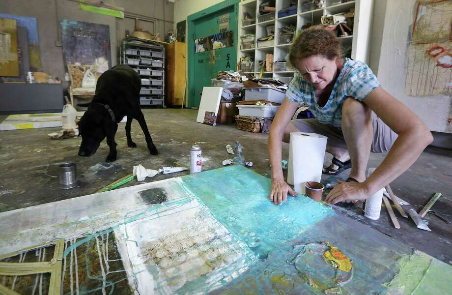 Cindy Palmer paints in her studio at High Wire Art as her dog Lila looks for a place to rest. Cindy and her husband Ray allow their dogs Zeke and Lila to roam their gallery studio space at High Wire Arts.  Monday, August 26, 2013. Photo: Bob Owen, San Antonio Express-News / © 2012 San Antonio Express-News