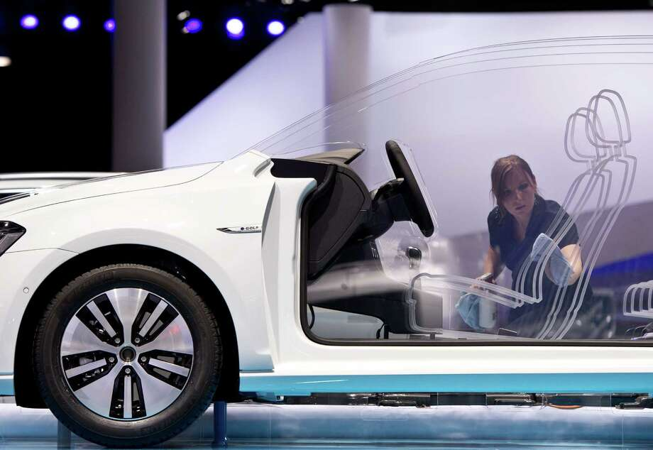 An employee cleans a cutaway model of the new Volkswagen e-Golf at the Frankfurt Auto Show in Frankfurt, Germany, Monday, Sept. 9, 2013 2013. Photo: AP