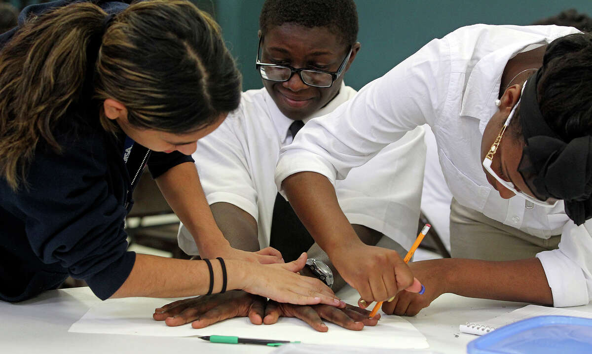 Niko Renfro has his hands traced by Patricia Castaneda (left) and Iesha White as Center City Health Carreers start the process of making murals on September 4, 2013.