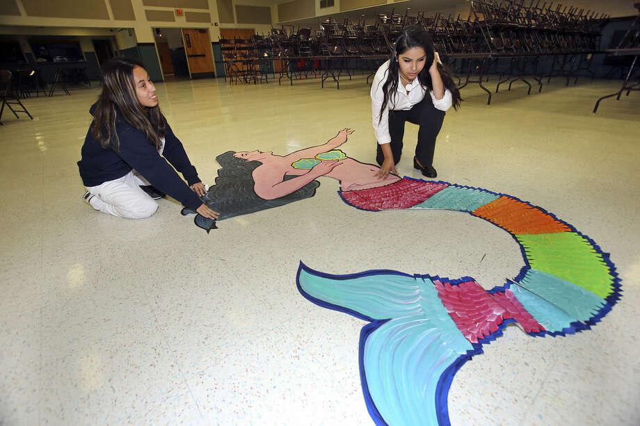 Patricia Castañeda (left) and Dora Azua unveil previous work during  City Center Health Careers' mural class.