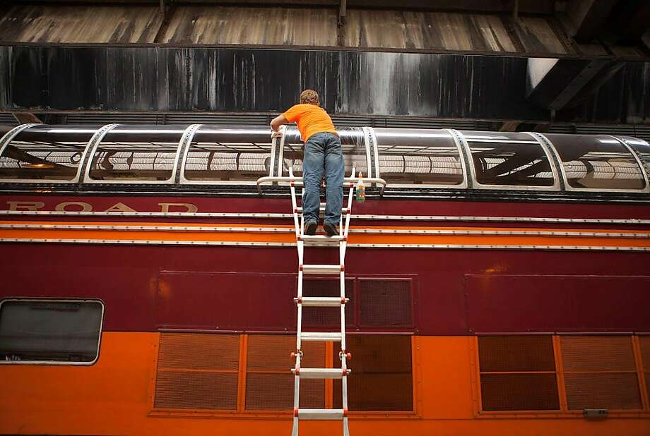 """A worker cleans the super-dome of the train carrying the """"Station to Station"""" nomadic art exhibition across the country. Photo: Mara McKevitt, Station To Station"""