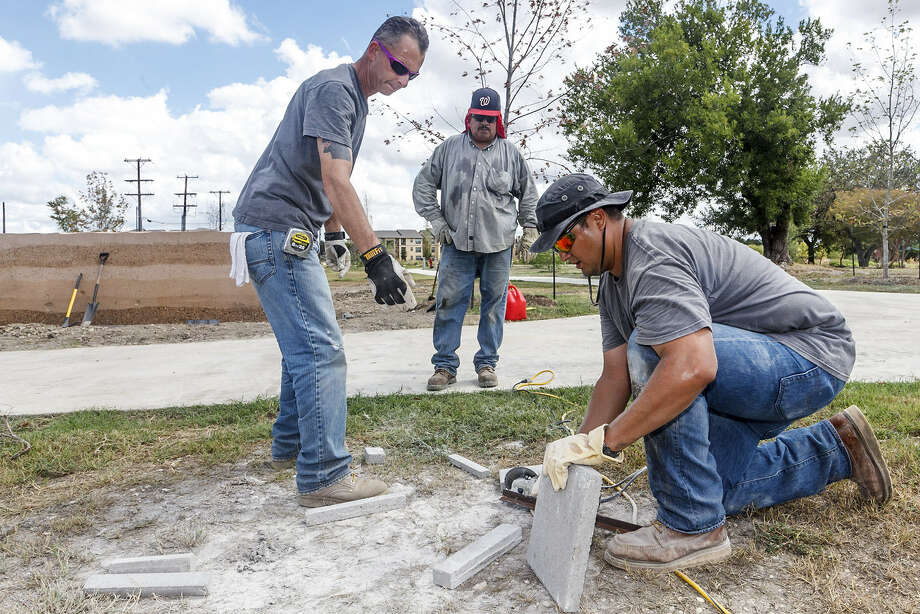 Workers with SpawGlass put the finishing touches on a monument at the entrance to the newly renamed Mission Park Pavilions on Monday. Shown, left to right, are Jim Colvin, Roland Garcia and Paul Onofre. Photo: Marvin Pfeiffer / Southside Reporter
