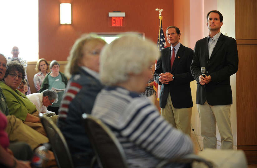 Sen. Richard Blumenthal, left, and Rep. Jim Himes listen statements and questions from a packed hous