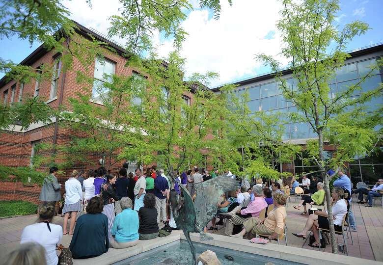 An overflow crowd listens from the courtyard as Rep. Jim Himes and Sen. Richard Blumenthal address a