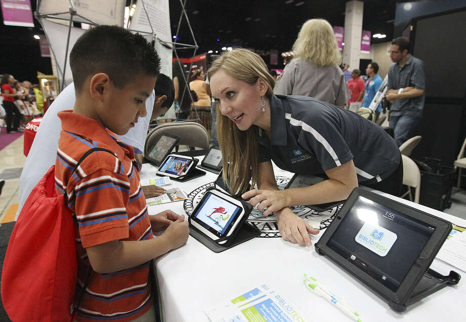 BiblioTech head librarian Ashley Eklof, right, demonstrates to Adonai Rodriguez, 9, how to use one of the interactive readers from the new BiblioTech, Bexar County's totally online library, at Festival People en Español at the Henry B. Gonzalez Convention Center on Aug. 31. BiblioTech opens to the public Saturday at 3505 Pleasanton Road. Photo: Kin Man Hui / San Antonio Express-News