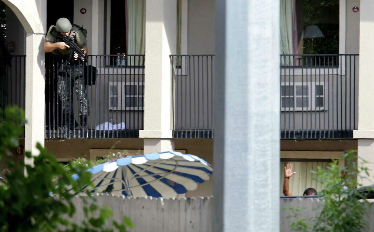 A San Antonio Police officer take aim at a shooting suspect at the Super 8 motel where the suspect shot a San Antonio police officer in the downtown area. The suspect was armed with a rifle and a gun at the motel located at 1614 N. St. Mary's, on Monday, Sept. 9, 2013.