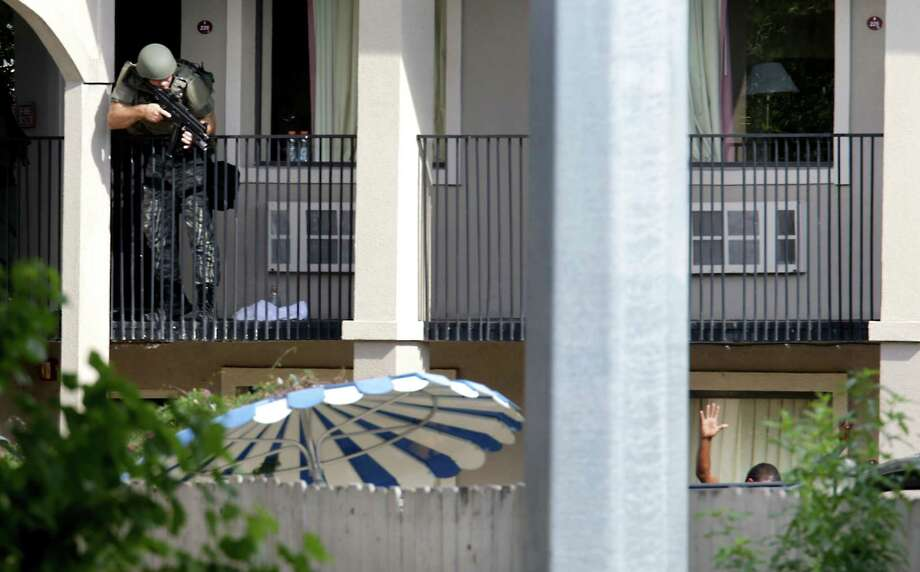 A San Antonio Police officer take aim at a shooting suspect at the Super 8 motel where the suspect shot a San Antonio police officer in the downtown area. The suspect was armed with a rifle and a gun at the motel located at 1614 N. St. Mary's, on Monday, Sept. 9, 2013. Photo: BOB OWEN, San Antonio Express-News / © 2012 San Antonio Express-News