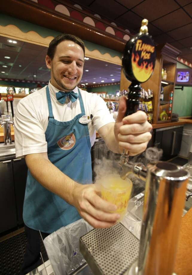 "The bartender serves up a Flaming Moe, a non-alcoholic beverage, at ""The Simpsons"" themed Moe's Tavern at Springfield USA at Universal Orlando. Photo: John Raoux, Associated Press"