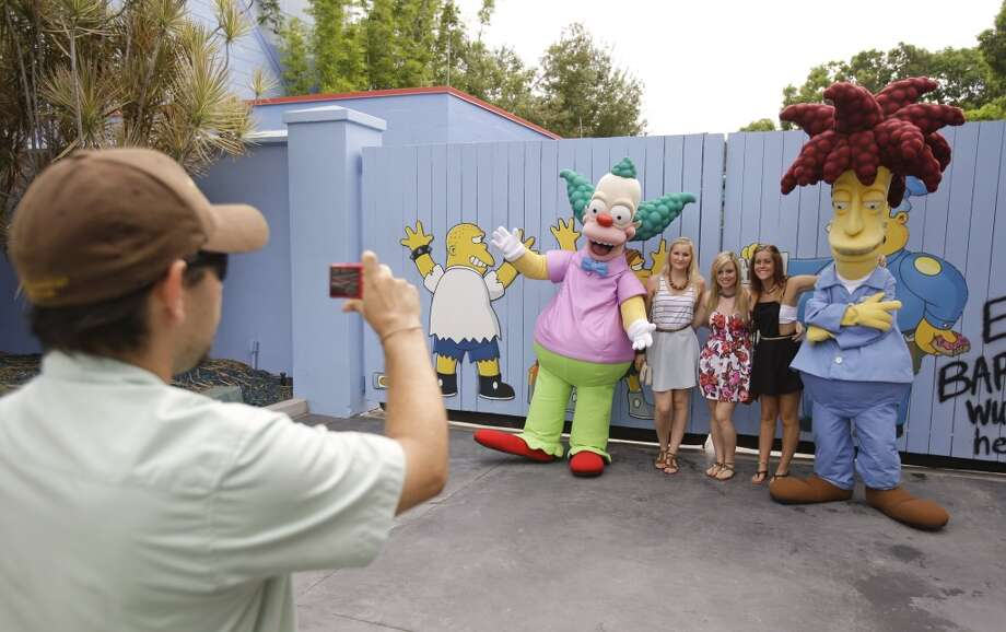 A park employee taking a photo of guests with characters from the animated series. Photo: John Raoux, Associated Press