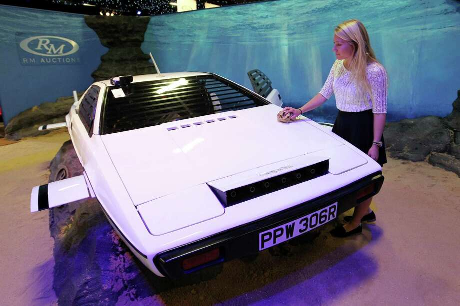 "RM Auctions assistant Hannah Fairclough with the white Lotus Esprit used in the James Bond movie ""The Spy Who Loved Me"", in London, Monday Sept. 9, 2013. The Lotus Esprit was sold Monday at a London auction for 550,000 pounds ($865,000). (AP Photo/PA, Sean Dempsey) UNITED KINGDOM OUT  NO SALES  NO ARCHIVE ORG XMIT: LON815 Photo: Sean Dempsey / PA"