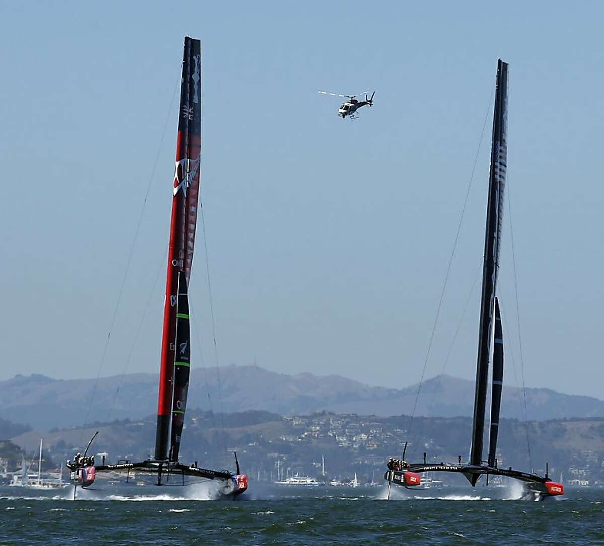 Oracle Team USA (right) and Emirates Team New Zealand boats compete towards the first marker during Race 2 of the America's Cup Finals on Saturday, September 7, 2013 in San Francisco, Calif.