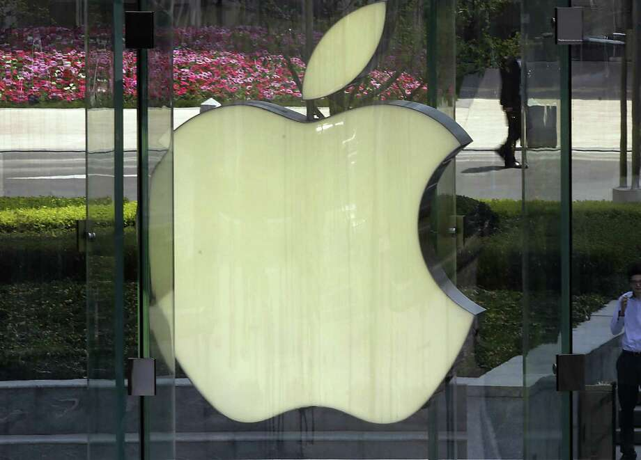 FILE - In this April 2, 2013, file photo, a man smokes near the logo of Apple in Shanghai. Apple is expected to unveil its latest version of the iPhone on Tuesday, Sept. 10, 2013. (AP Photo/Eugene Hoshiko, File) ORG XMIT: NY119 Photo: Eugene Hoshiko / AP