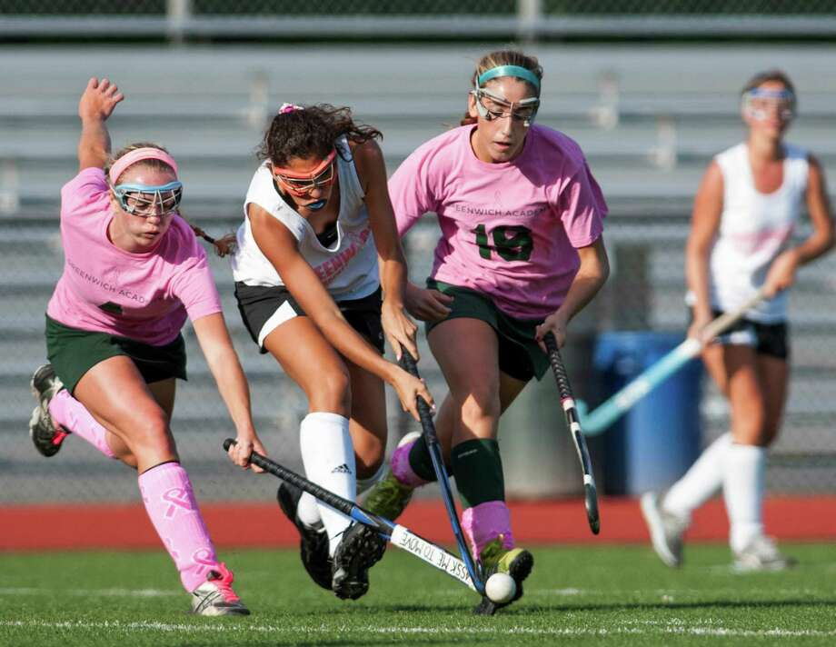 Greenwich Academy's Katrina Kraus and Sasha Fritts battle Greenwich high school's Tania Iskandar (center) for the ball during a girls field hockey game played at Greenwich high school, Greenwich, CT on Monday September 9th, 2013. Photo: Mark Conrad / Stamford Advocate Freelance