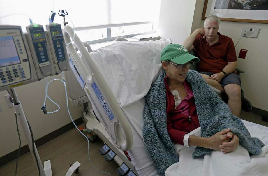 Bev Veals, accompanied by her husband Scott, undergoes chemotherapy treatment in Durham, N.C. Photo: Gerry Broome / Associated Press