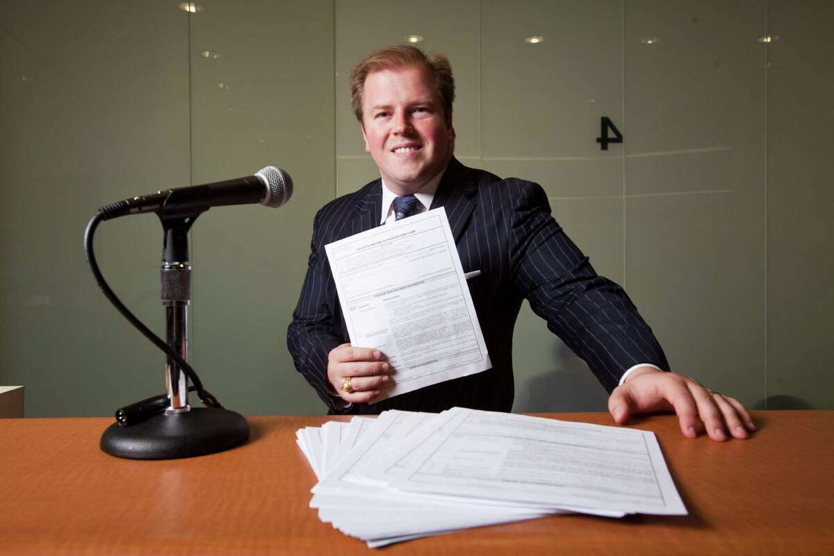 Harris County District Clerk Chris Daniel holds a form that allows prospective jurors to donate their payment for their first day of service to charity, Dec. 12, 2012 in Houston at a jury assembly room.