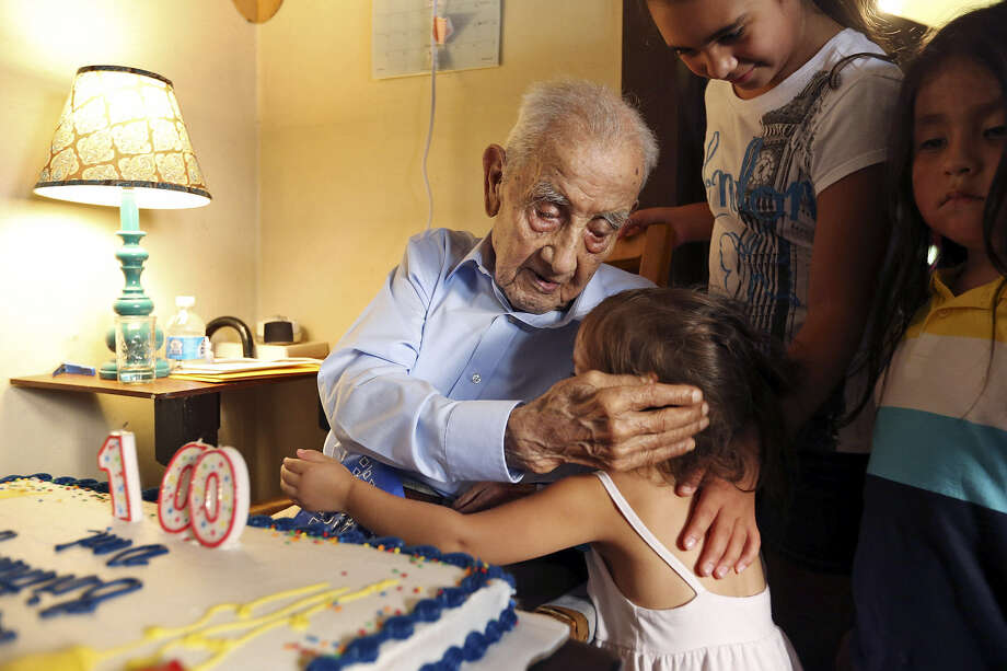Above: Alfonso Morales hugs his great-granddaughter Abigail Garcia, 2,  during his 100th birthday party Aug. 4 at his home.                    Top: A group of men and boys pause for this undated photo as they pick cotton in a Texas field. Alfonso Morales is fourth from left. Photo: Edward A. Ornelas / San Antonio Express-News