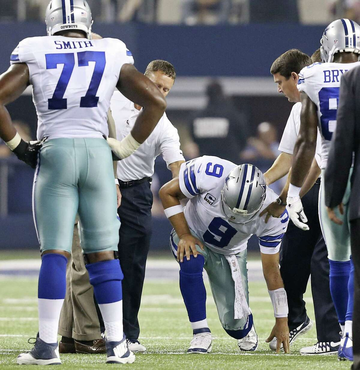 Cowboys QB Tony Romo is helped to his feet by team trainers after being sandwiched by Giants pass rushers Mathias Kiwanuka and Justin Trattou on Sunday night. X-rays of Romo's rib area on Monday revealed no structural damage.
