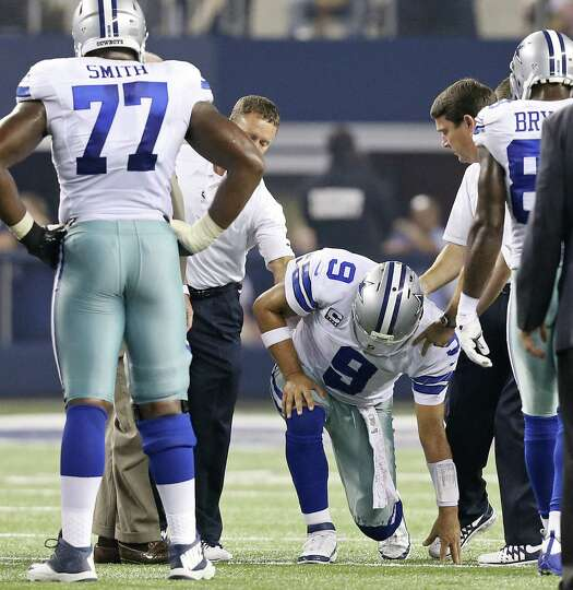 Cowboys QB Tony Romo is helped to his feet by team trainers after being sandwiched by Giants pass ru