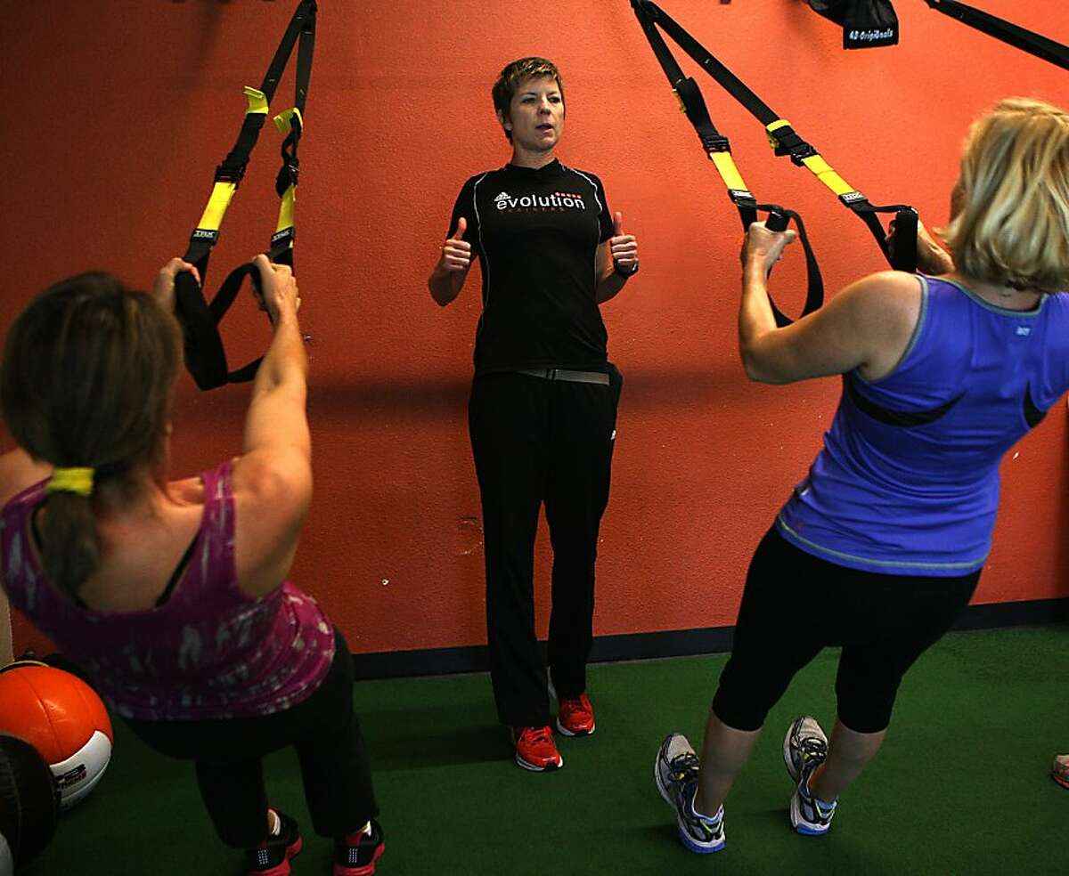 Ashley Selman (middle) shows how to do pull ups while training Carmen Ventura (left) and Susan Barclay (right) from Menlo Park in a Total Body Evolution Class in Mountain View, California on Tuesday, September 3, 2013. She had a hip replacement in May. Ashley was a former javelin champion and is now a trainer and owner of Evolution Trainers.