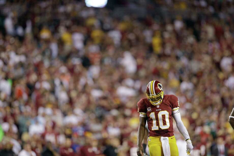 Washington Redskins quarterback Robert Griffin III walks across the field during the first half of a NFL football game against the Philadelphia Eagles in Landover, Md., Monday Sept. 9, 2013. (AP Photo/Patrick Semansky) Photo: Patrick Semansky, Associated Press / AP