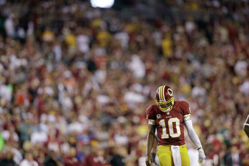 Washington Redskins quarterback Robert Griffin III walks across the field during the first half of a