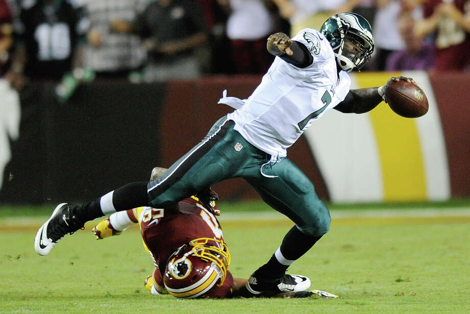 Philadelphia Eagles quarterback Michael Vick (7) looks for an opening to pass as Washington Redskins inside linebacker Perry Riley gets tangled up in his legs during the first half of an NFL football game in Landover, Md., Monday, Sept. 9, 2013. (AP Photo/Nick Wass) ORG XMIT: FDX117 Photo: Nick Wass / FR67404 AP